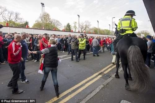 Напряженность монтажные: полицейский officeer на лошади осматривает сцену, как разгневанные сторонники столкновение