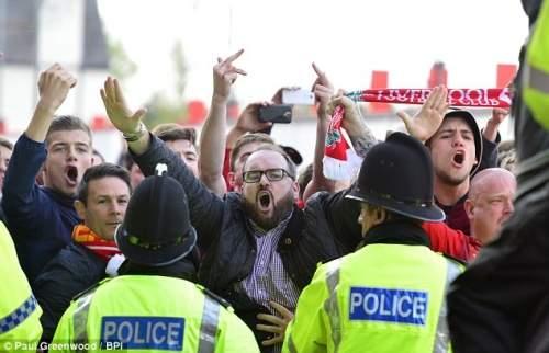 Сдерживается: Полиция выступать в качестве баррикад, как болельщики Ливерпуля петь и петь вне конце Энфилд Роуд